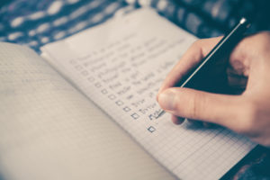 A hand writing list of goals on notepad.